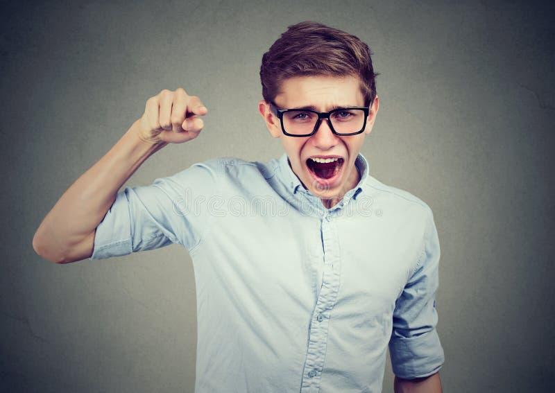 Hombre enojado del adolescente que acusa alguien que grita señalando el finger imágenes de archivo libres de regalías