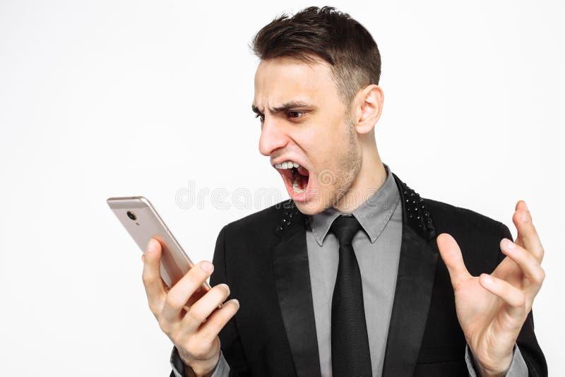 Hombre enojado del negocio, en un traje negro, gritando con cólera en un SM fotografía de archivo libre de regalías