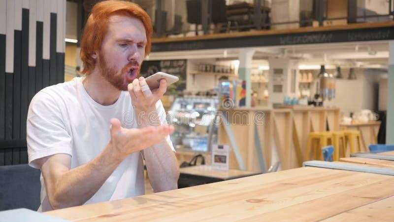 Hombre enojado del pelirrojo que grita, hablando en el teléfono móvil en café imagenes de archivo