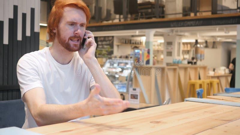 Hombre enojado del pelirrojo que habla en el teléfono móvil foto de archivo