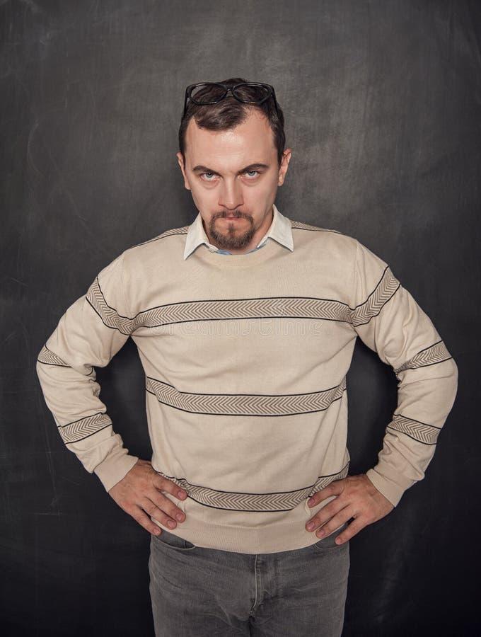 Hombre enojado divertido del profesor en la pizarra imagen de archivo libre de regalías