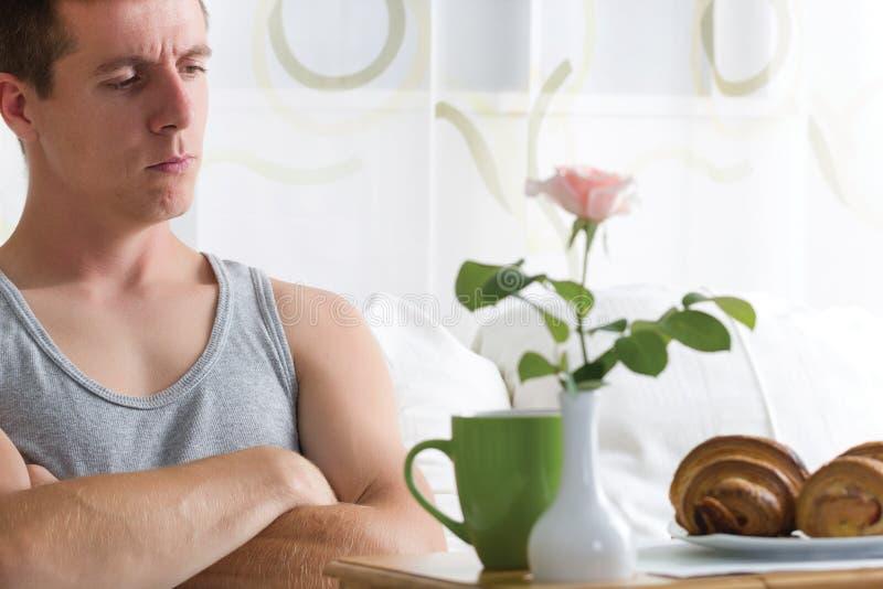 Hombre enojado en esperar de la cama imagenes de archivo