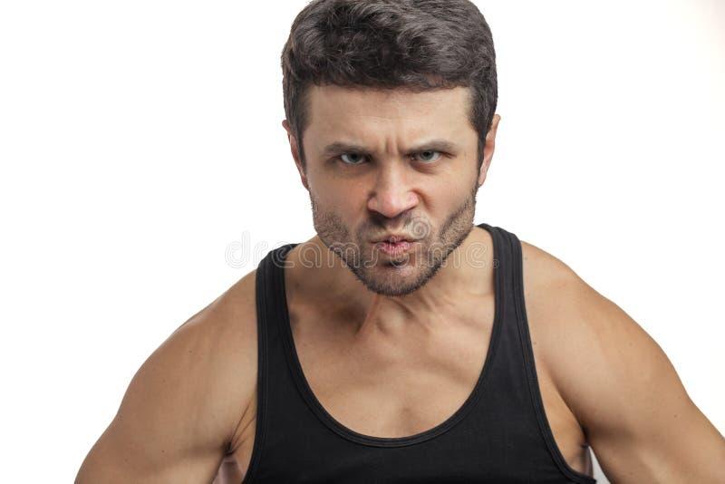 Hombre enojado en ropa de deportes el hombre fuerte es caída en una rabia foto de archivo