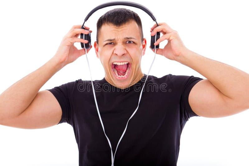 Hombre enojado que escucha la música ruidosa con los auriculares imagen de archivo