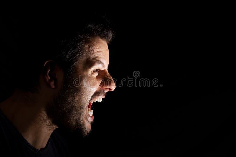 Hombre enojado que grita hacia fuera aislado ruidosamente en fondo negro fotografía de archivo libre de regalías