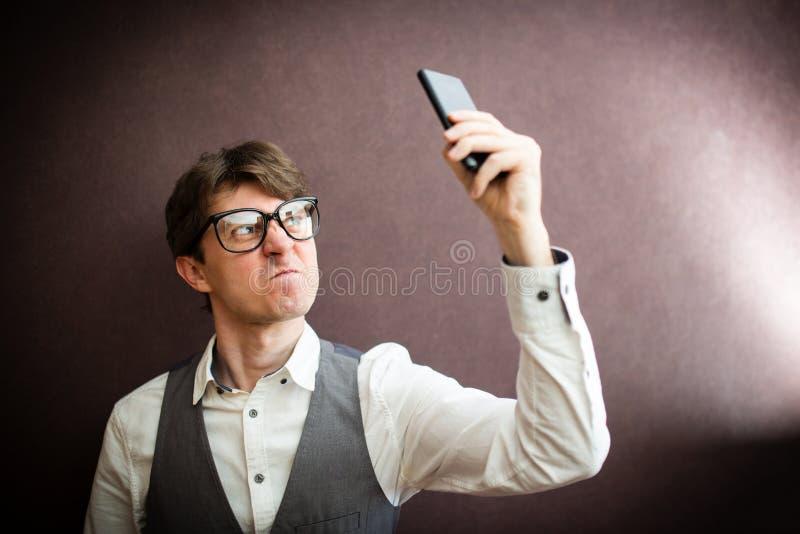 Hombre enojado que usa smartphone móvil imagenes de archivo