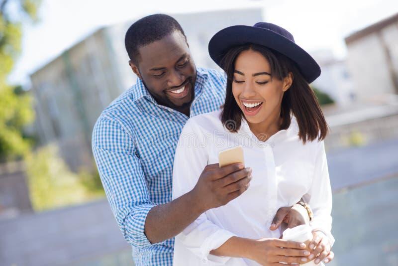 Hombre entusiasta encantador que comparte algo interesante con su novia fotos de archivo