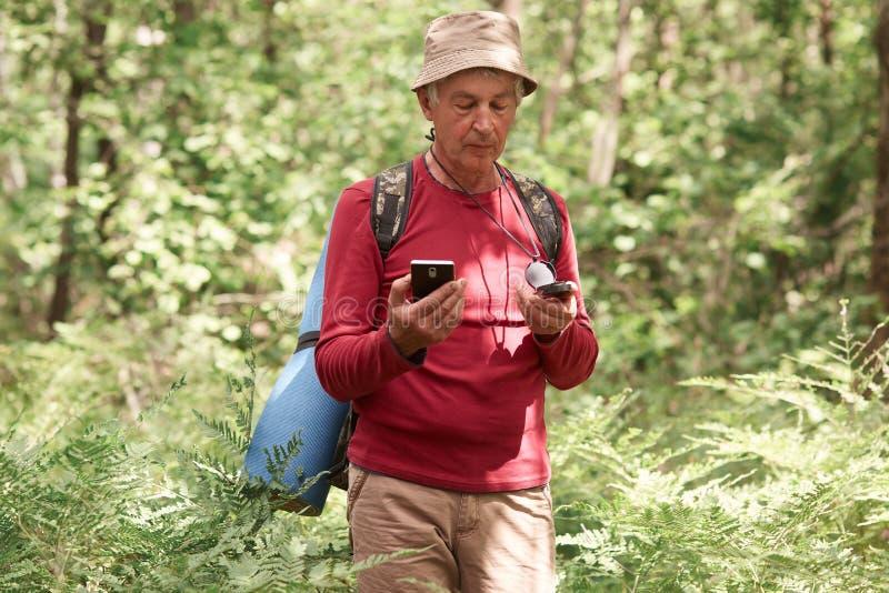Hombre entusiasta serio que vaga en bosque, sosteniendo el compás y el smartphone en sus manos, eligiendo su ruta del viaje, sien fotos de archivo