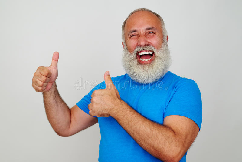 Hombre envejecido alegre que sonríe sinceramente y que da dos pulgares para arriba foto de archivo libre de regalías