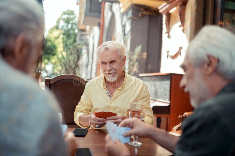 Hombre envejecido barbudo serio que juega con los amigos foto de archivo