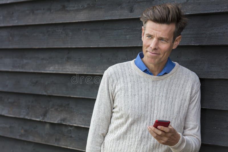 Hombre envejecido centro feliz que usa el teléfono celular móvil imagen de archivo libre de regalías