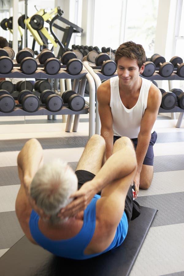 Hombre envejecido centro que trabaja con el instructor personal In Gym fotos de archivo