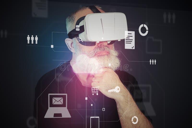 Hombre envejecido en auriculares de la realidad virtual delante del scre interactivo fotografía de archivo libre de regalías