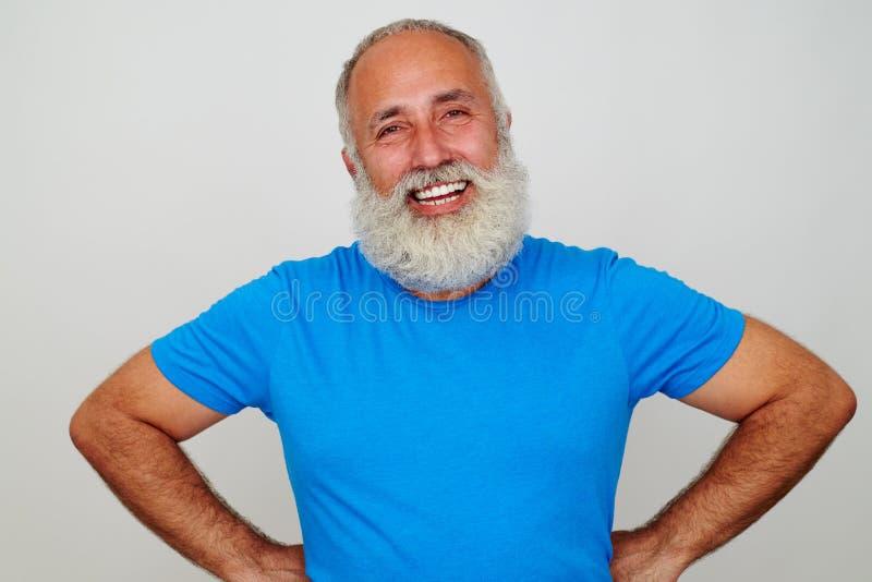 Hombre envejecido hermoso que se coloca con las manos en caderas y la sonrisa imágenes de archivo libres de regalías