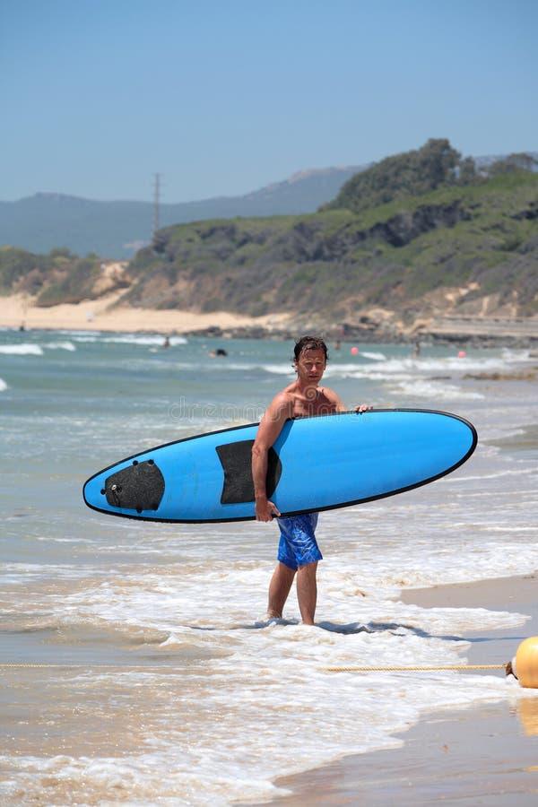 Hombre envejecido medio apto que practica surf en la playa en verano fotografía de archivo