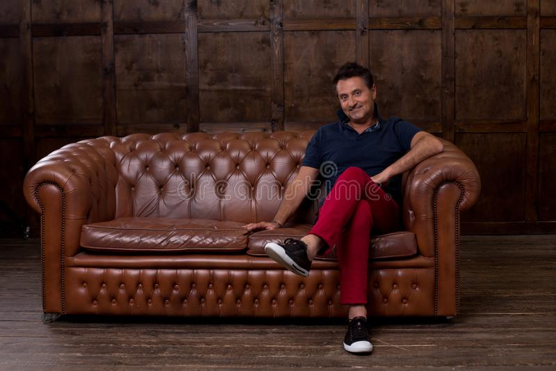 Hombre envejecido medio positivo que siente alegre y que sonríe mientras que estando en el cuarto lacónico y sentándose en el sof imagen de archivo libre de regalías