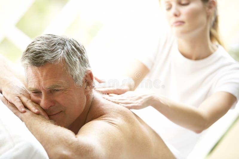 Hombre envejecido medio que disfruta de masaje imagen de archivo libre de regalías