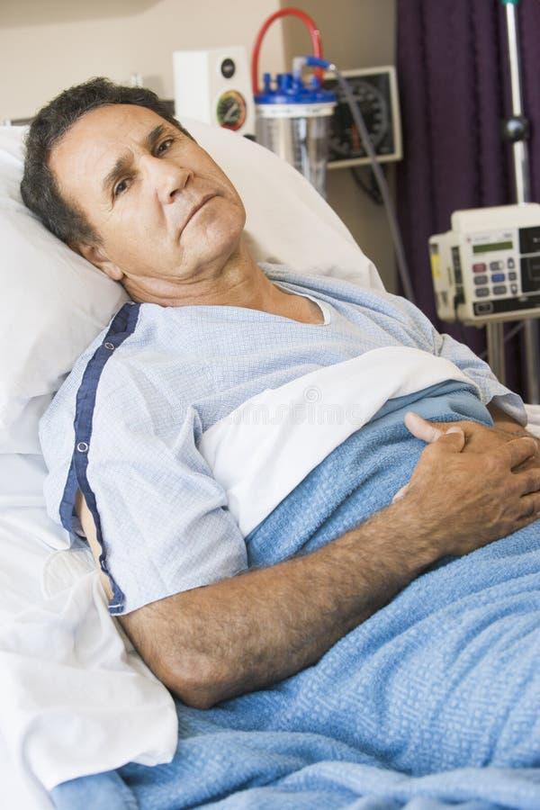 Hombre envejecido medio que miente en cama de hospital foto de archivo libre de regalías
