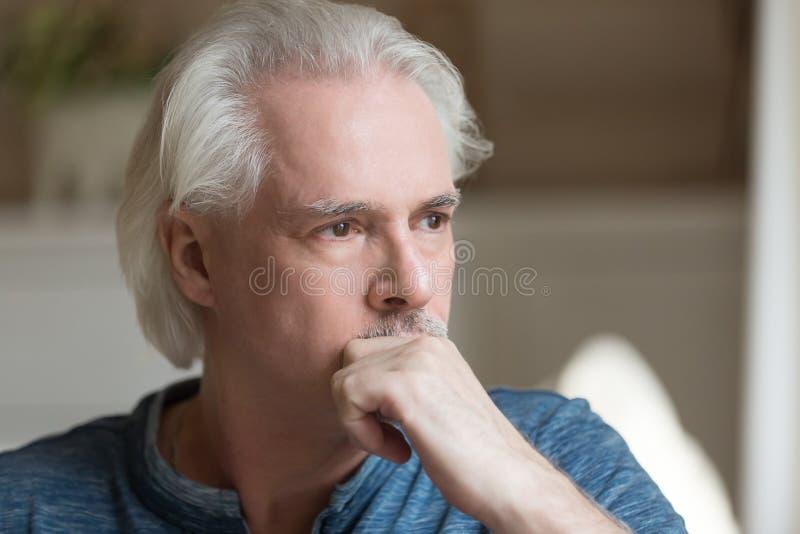 Hombre envejecido pensativo que mira en la distancia perdida en pensamientos fotos de archivo libres de regalías