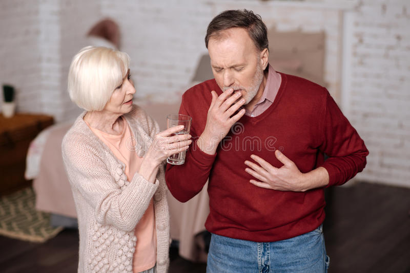 Hombre envejecido que tose mientras que su esposa que le ayuda fotografía de archivo libre de regalías