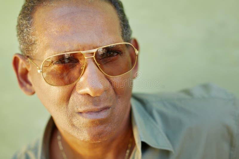 Hombre envejecido serio con las gafas de sol que miran la cámara fotografía de archivo libre de regalías