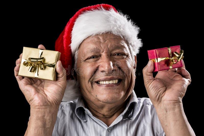 Hombre envejecido sonriente que sostiene dos pequeños regalos de Navidad imagenes de archivo