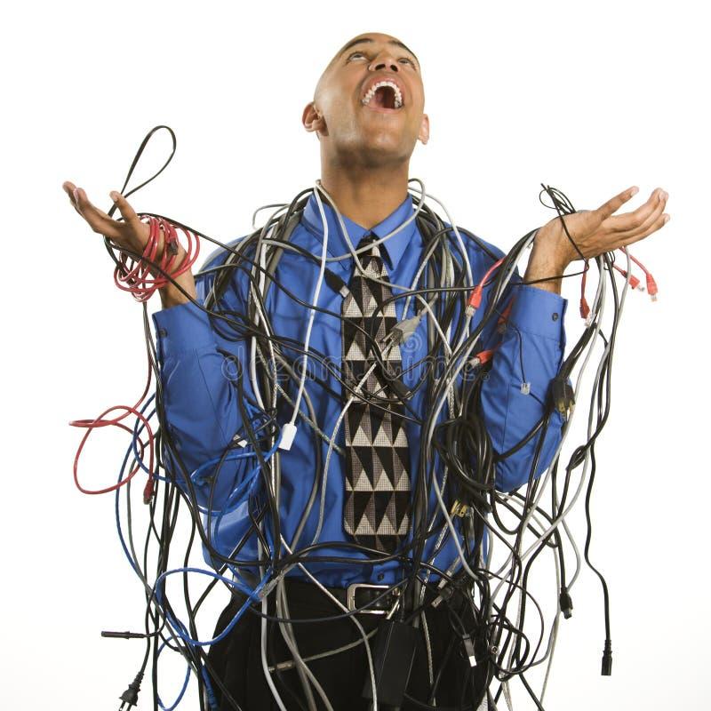 Hombre envuelto en cables. fotografía de archivo