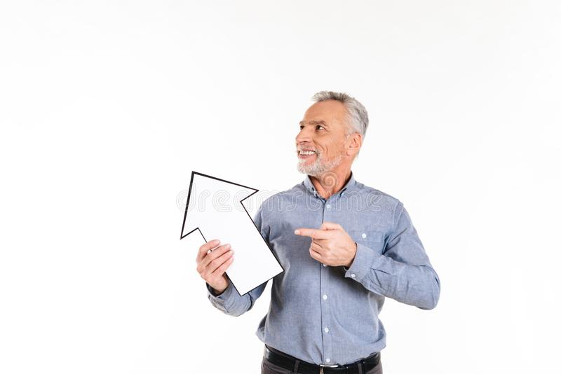 Hombre esperanzado sonriente que sostiene la flecha que señala en el espacio de la copia aislada imagenes de archivo
