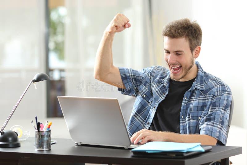 Hombre eufórico del ganador que usa un ordenador portátil en casa imagen de archivo