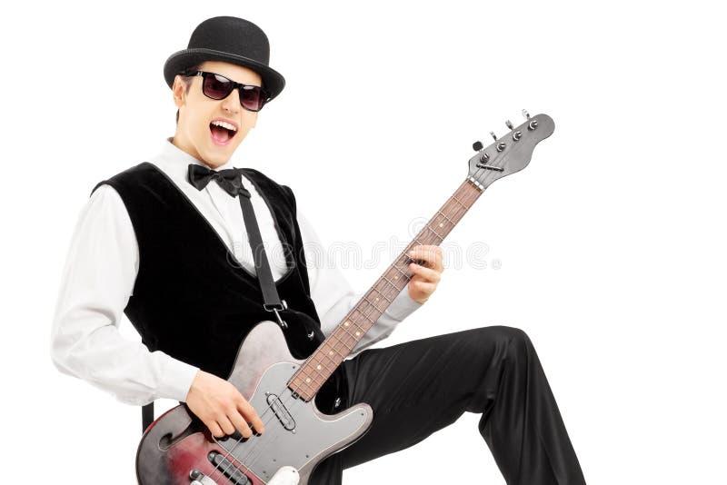 Hombre eufórico que toca una guitarra baja fotografía de archivo