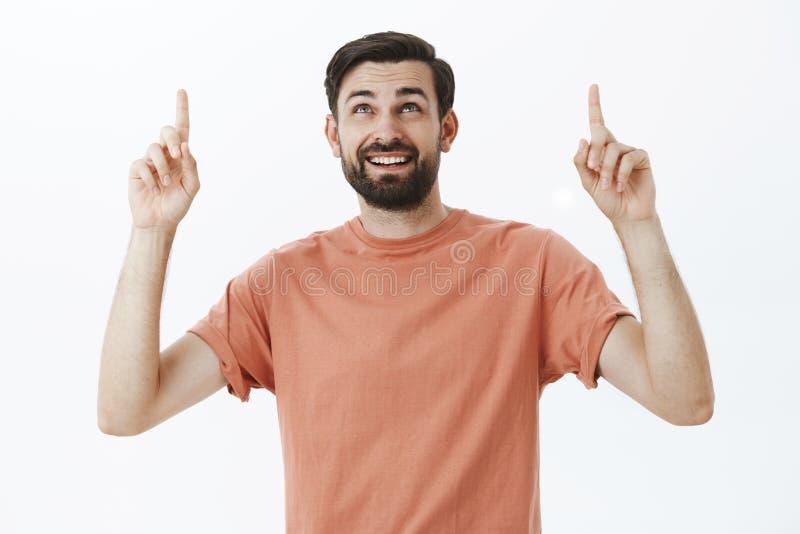Hombre europeo atractivo curioso feliz con la barba oscura en la camiseta casual que aumenta los dedos índices que miran y que de fotografía de archivo libre de regalías