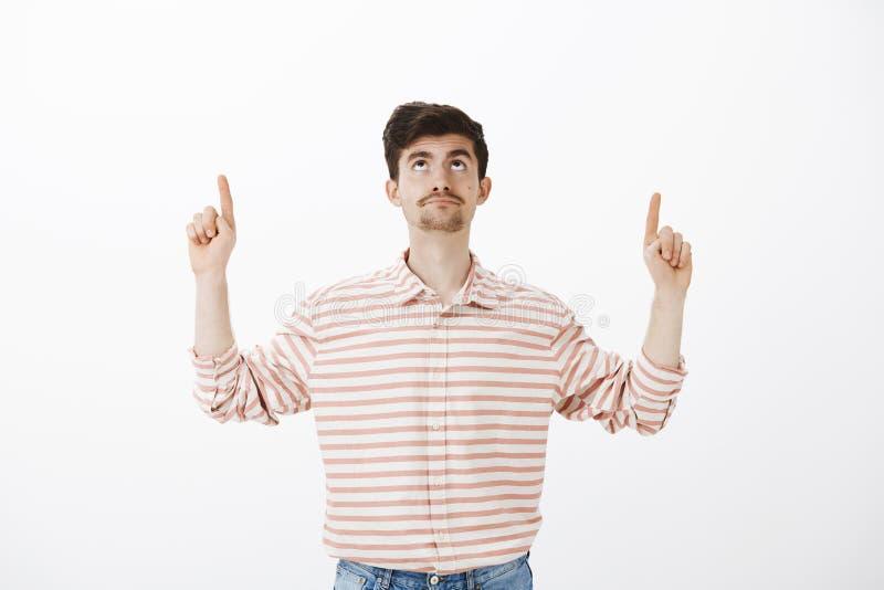 Hombre europeo atractivo descontentado intenso con la barba, mirando y destacando con la expresión decepcionada, siendo fotografía de archivo libre de regalías