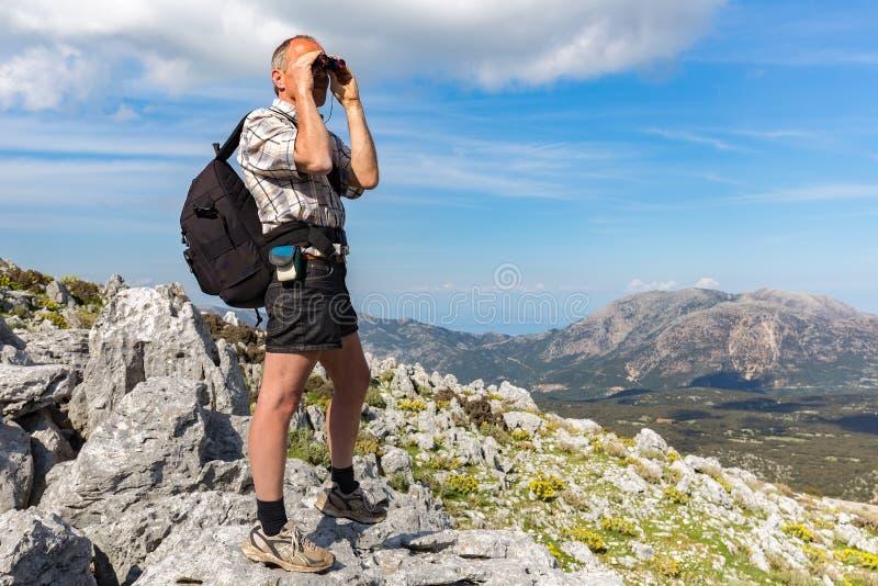 Hombre europeo en las rocas que miran a través de los prismáticos imagen de archivo libre de regalías