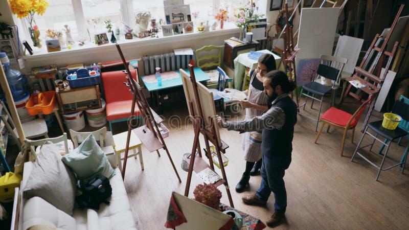 Hombre experto del artista que enseña a la pintura de la mujer joven en el caballete en el estudio de la escuela de arte - gente  fotos de archivo libres de regalías