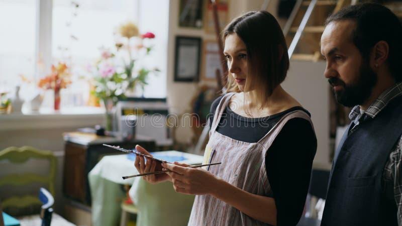 Hombre experto del artista que enseña a la pintura de la mujer joven en el caballete en el estudio de la escuela de arte - gente  fotos de archivo