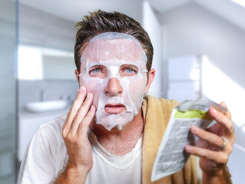 Hombre extra?o y divertido joven en casa intentando usando m?scara facial del papel de la belleza el limpiamiento aprendiendo la  fotos de archivo