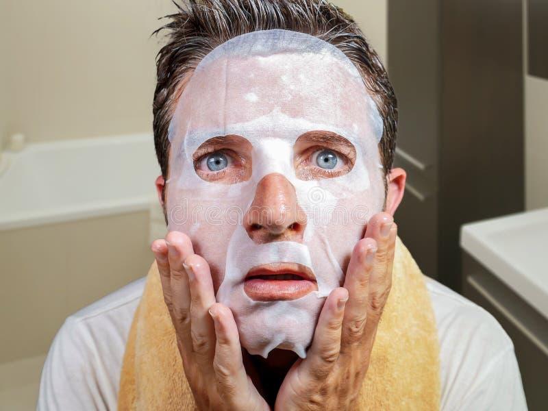 Hombre extra?o y divertido joven en casa que intenta usando la m?scara facial del papel de la belleza que limpia aprendiendo el t imágenes de archivo libres de regalías
