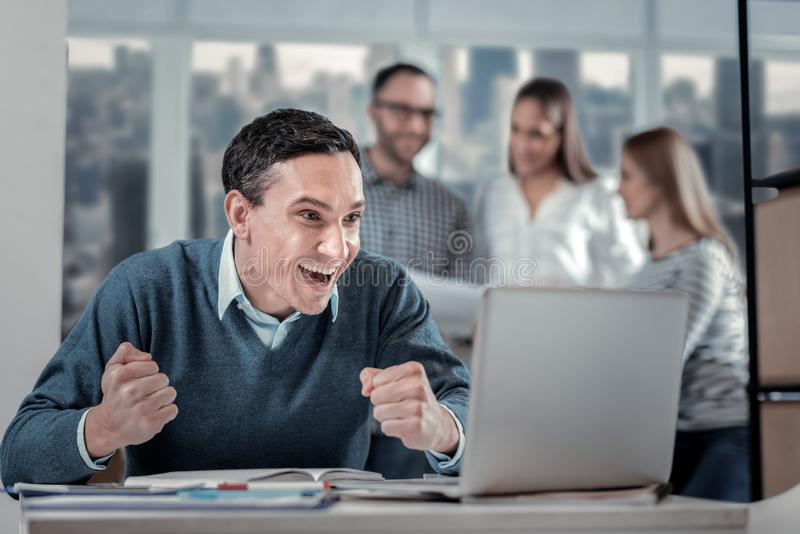 Hombre exuberante que se sienta en su ordenador portátil fotos de archivo libres de regalías