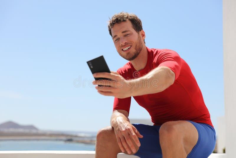 Hombre físico del instructor del selfie del teléfono de la aptitud que toma la foto o que registra el vlog video Persona joven de imágenes de archivo libres de regalías