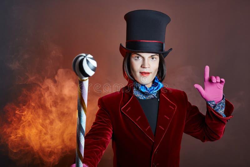 Hombre fabuloso del circo en un sombrero y un traje rojo que presentan en el humo en un fondo oscuro coloreado Un payaso en un pa imágenes de archivo libres de regalías