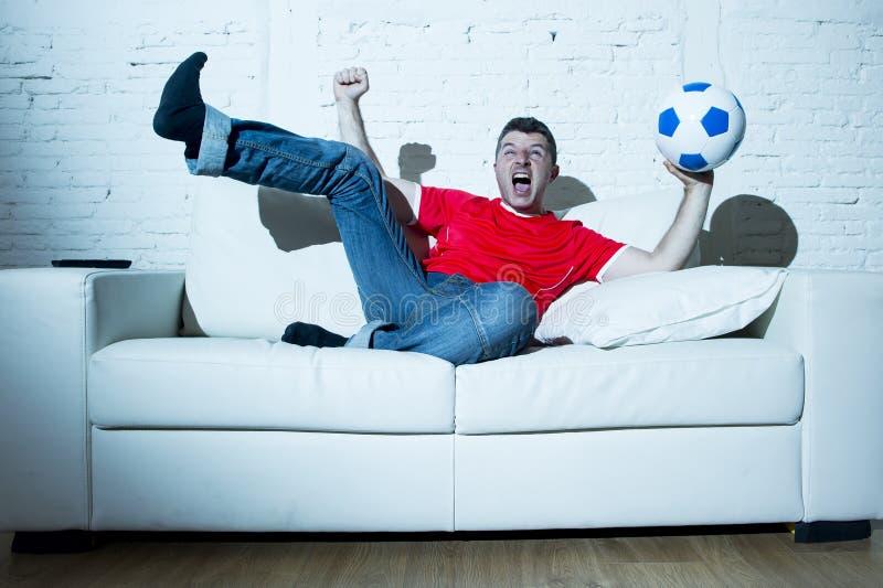 Hombre fanático loco como juego de observación del fanático del fútbol en la televisión que lleva el jersey de equipo rojo que ce fotografía de archivo
