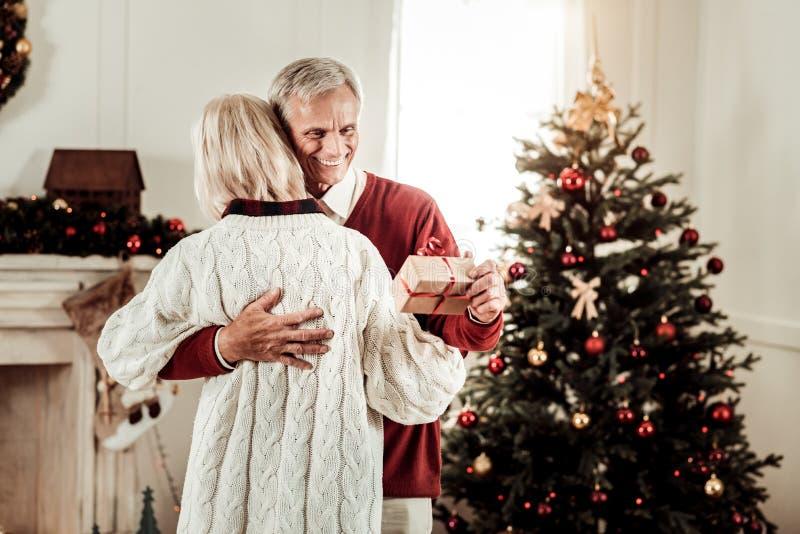 Hombre feliz alegre que abraza a su esposa y que lleva a cabo un presente imagen de archivo libre de regalías