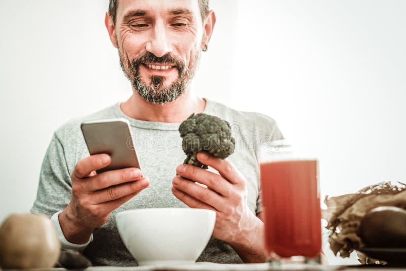 Hombre feliz alegre que mira el bróculi fotografía de archivo libre de regalías