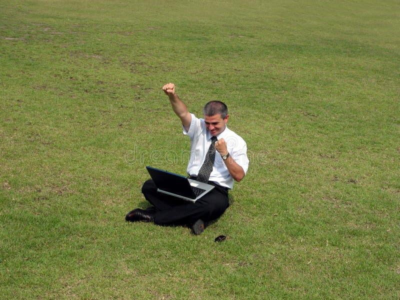 Hombre feliz con el ordenador en el campo