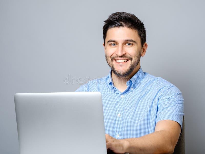 Hombre feliz con el ordenador portátil aislado en gris fotos de archivo libres de regalías