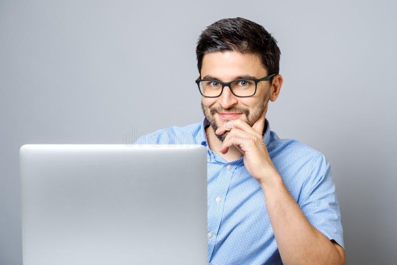 Hombre feliz con el ordenador portátil aislado en gris fotos de archivo