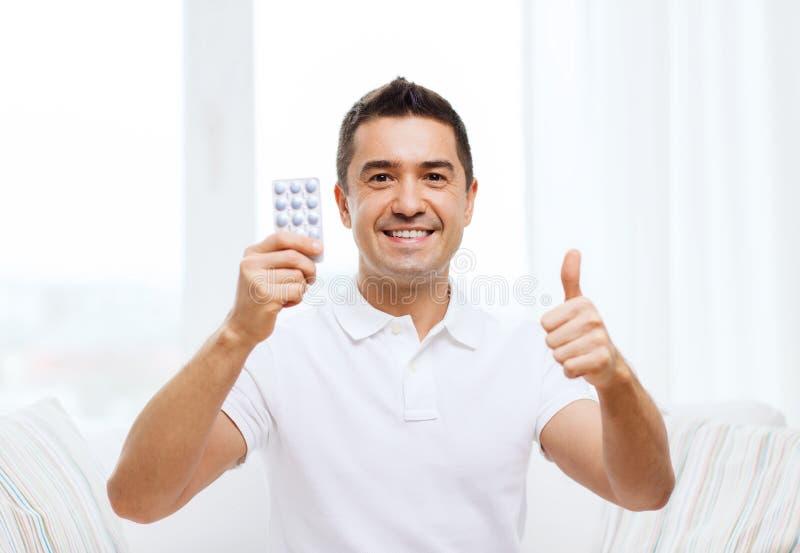 Hombre feliz con el paquete de píldoras que muestran los pulgares para arriba fotos de archivo libres de regalías