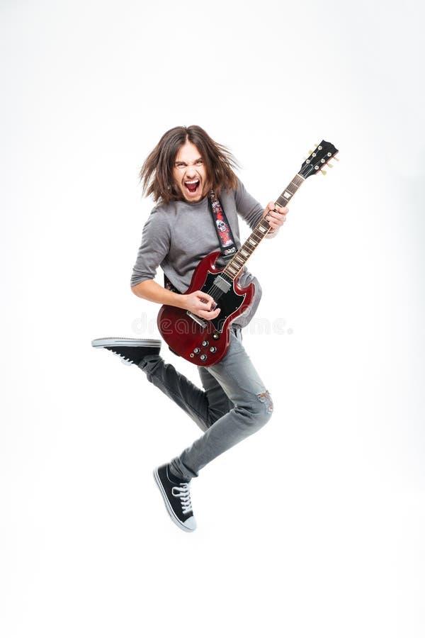 Hombre feliz con el pelo largo que salta y que toca la guitarra eléctrica fotografía de archivo