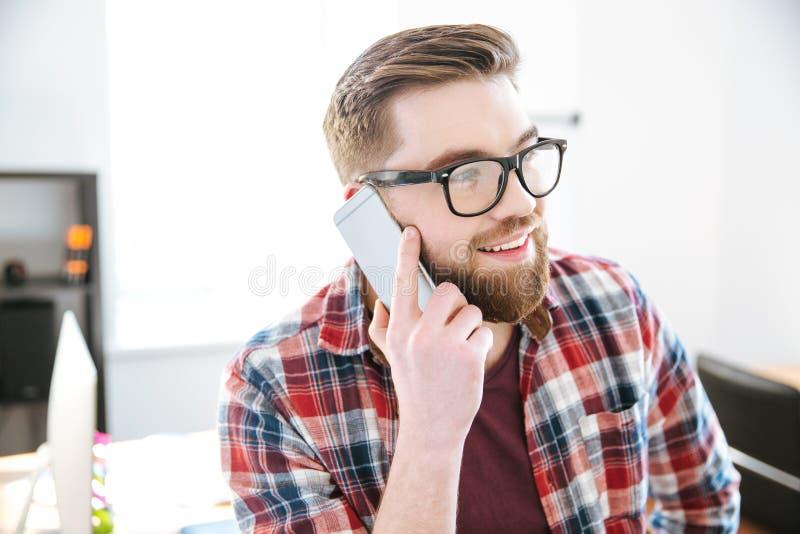 Hombre feliz con la barba en vidrios que habla en el teléfono celular imágenes de archivo libres de regalías