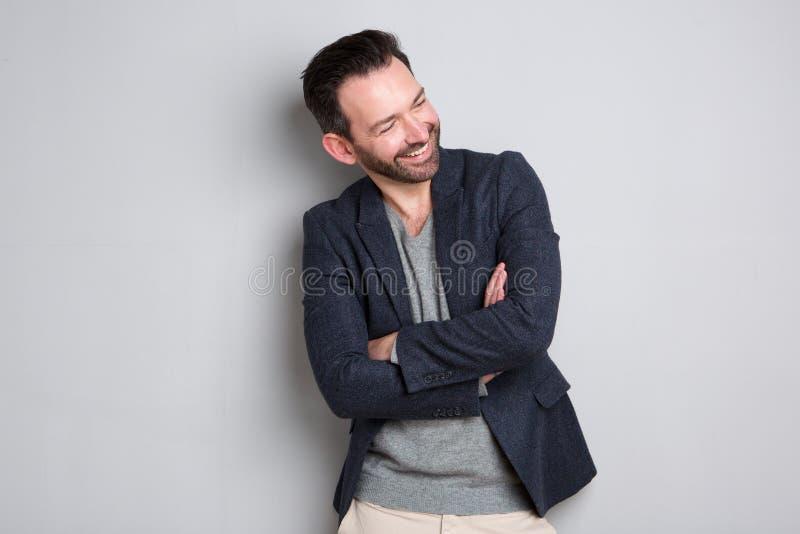 Hombre feliz con la barba que ríe con los brazos cruzados fotografía de archivo libre de regalías